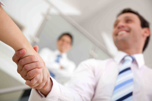 Business man handshaking a person in an office